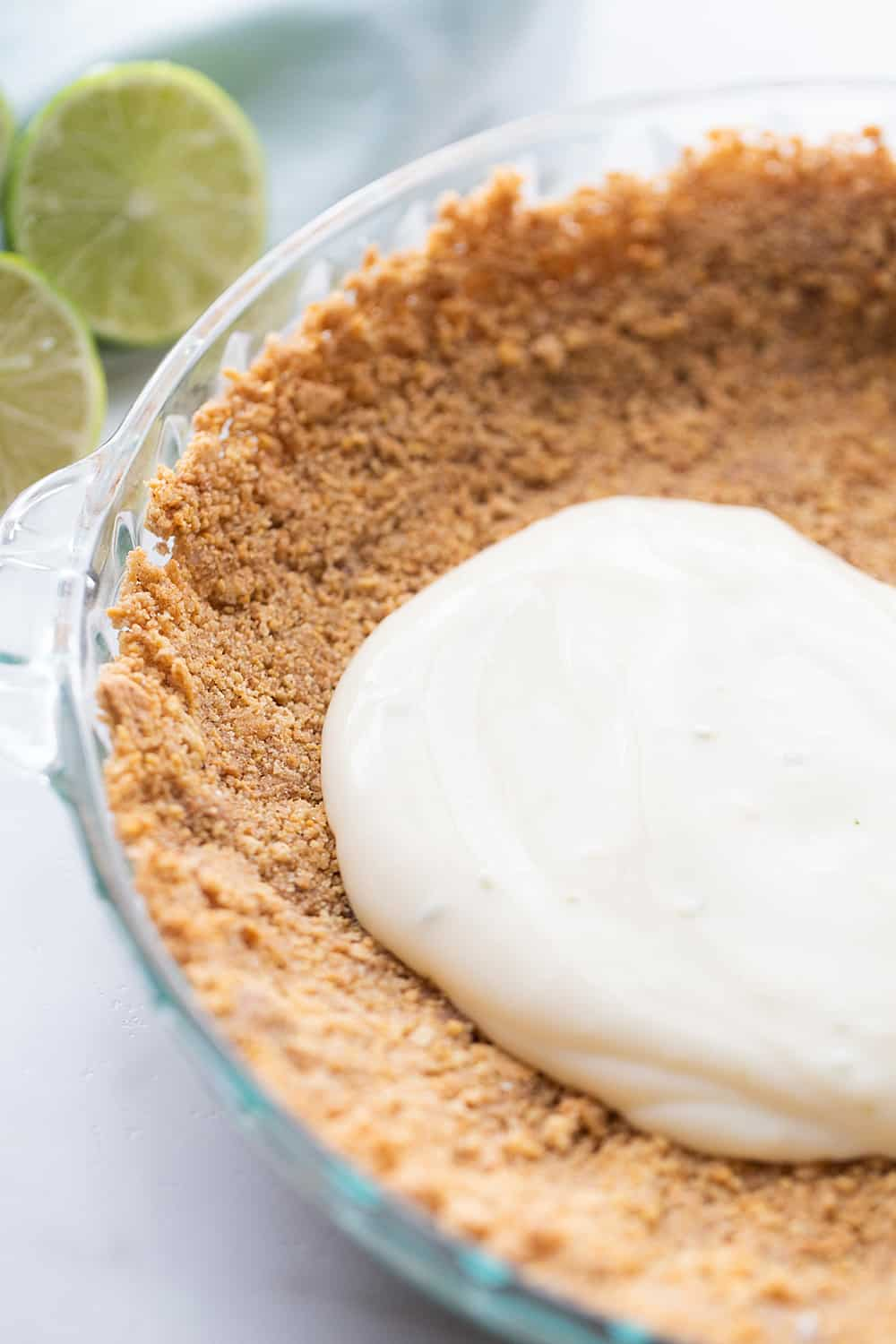 Easy Key Lime Pie with Homemade Whipped Cream - This easy key lime pie calls for a homemade graham cracker crust and the easiest pie filling ever. Top it with homemade whipped cream and it's always a hit! #keylime #keylimepie #whippedcream #dessert #baking #pie #lime #halfscratched