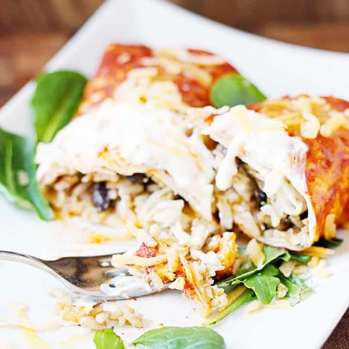 Enchilada style burritos feature enchilada sauce, dirty rice, and a versatile recipe that makes enough for two 9x13-inch pans. That means you can bake one tonight and freeze one for a future Taco Tuesday!   halfscratched.com #burrito #enchiladas #freezermeal #mexican #mexicanfood #mexicanrecipe #tacotuesday #cincodemayo