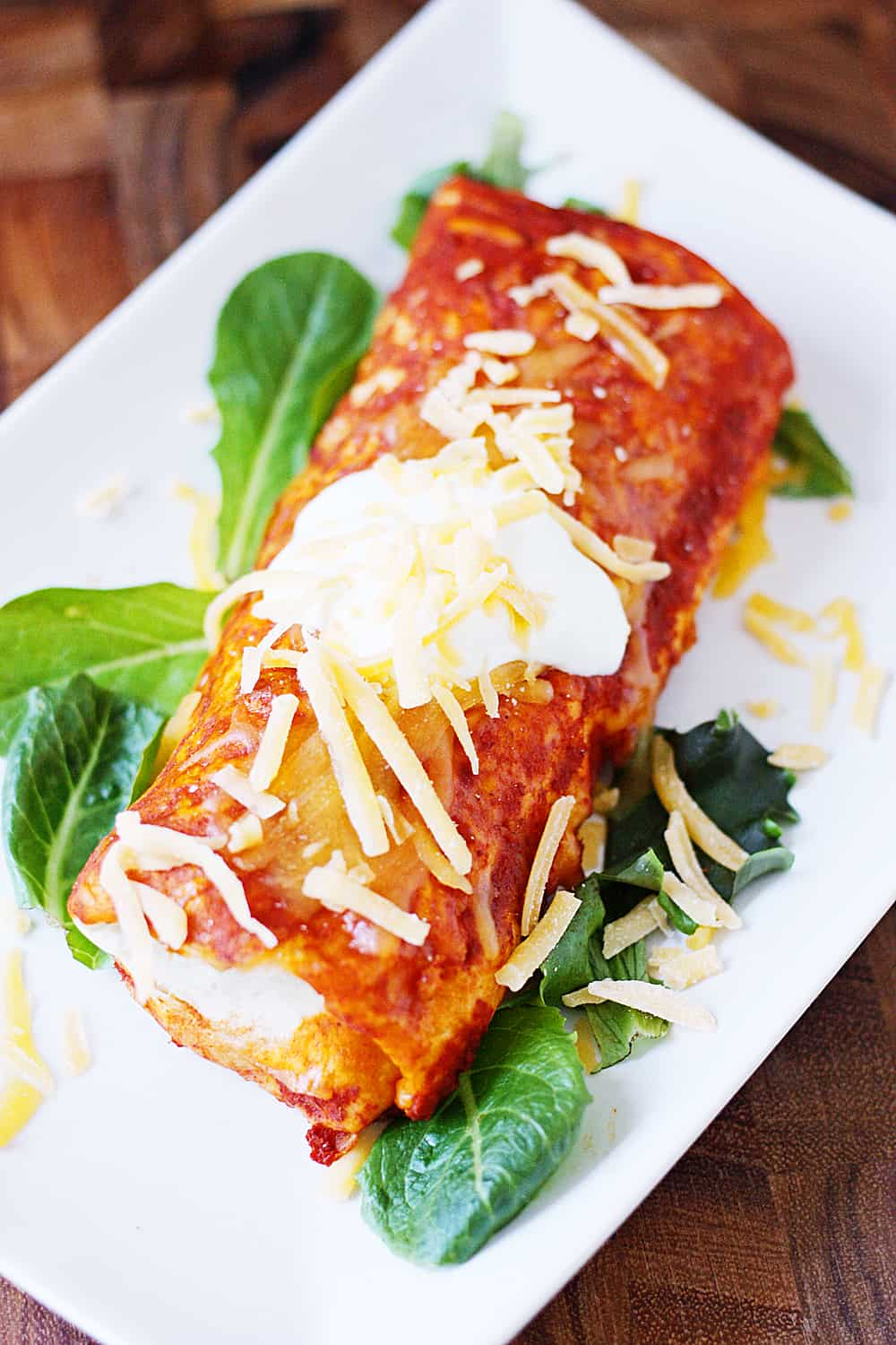 Enchilada style burritos feature enchilada sauce, dirty rice, and a versatile recipe that makes enough for two 9x13-inch pans. That means you can bake one tonight and freeze one for a future Taco Tuesday! | halfscratched.com #burrito #enchiladas #freezermeal #mexican #mexicanfood #mexicanrecipe #tacotuesday #cincodemayo