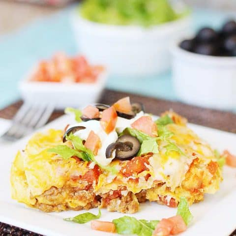 Mexican Lasagna -- Mexican lasagna features layers of tortillas, taco meat, refried beans, salsa, cheese, and more cheese. Top with your favorite taco toppings and you have an easy weeknight Mexican recipe the entire family will love! #mexican #lasagna #tacotuesday #mexicanrecipe #easyrecipe