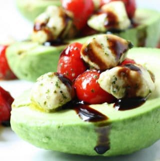 Caprese Stuffed Avocado -- Caprese stuffed avocado is one of the best ways to eat caprese salad with its creamy mozzarella, cherry tomatoes, and balsamic glaze atop ripe avocado.