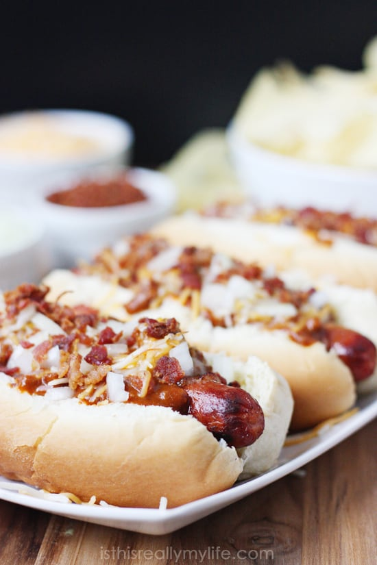 Double Bacon Chili Cheese Dog - hot dogs wrapped with bacon, grilled and topped with chili, cheese, onion and more bacon! Recipe from halfscratched.com