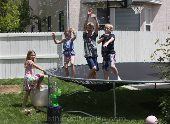 Kids jumping on the trampoline with bubbles