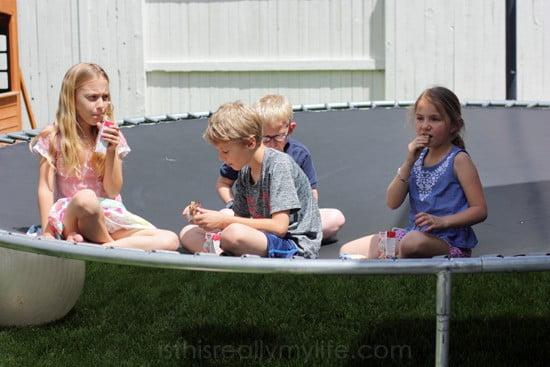 Kids taking a snack break on the trampoline