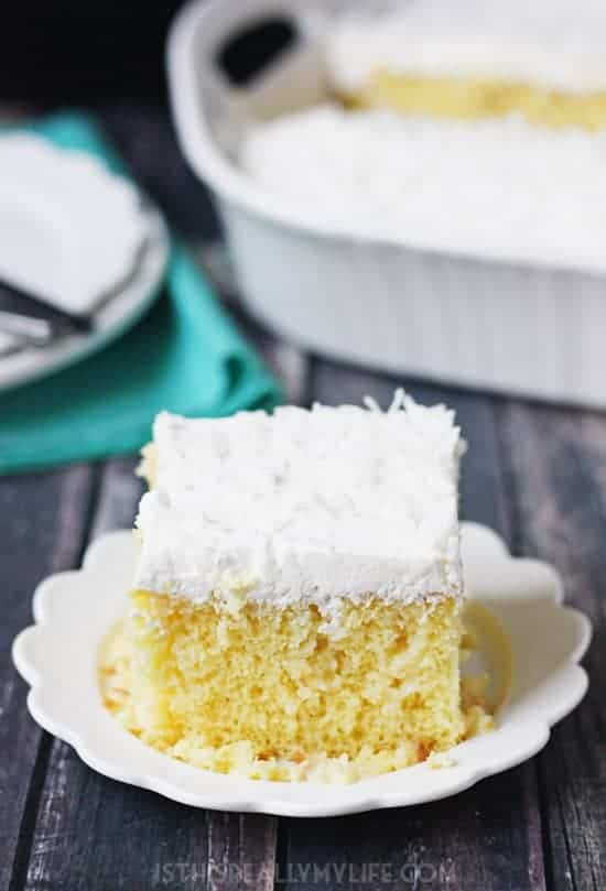 Coconut Poke Cake -- This coconut poke cake features a yellow cake infused with sweet coconut cream and topped with homemade whipped cream frosting and shredded coconut. | #pokecake #cake #coconut #cake #halfscratched #baking #easyrecpi #dessert #dessertrecipe