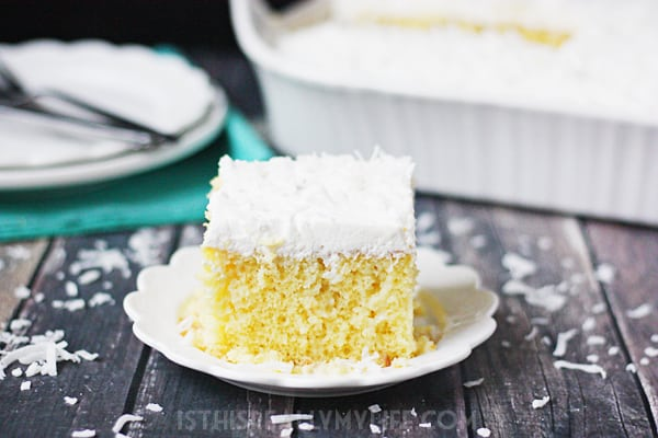 Coconut Poke Cake -- This coconut poke cake features a yellow cake infused with sweet coconut cream and topped with homemade whipped cream frosting and shredded coconut.