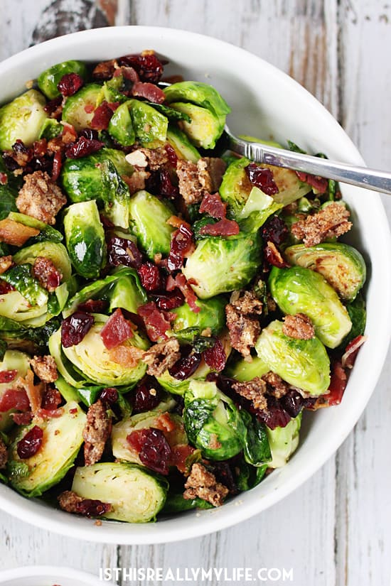 Sauteed Brussels Sprouts with Bacon -- Sauteed brussels sprouts turn into the most scrumptious side dish after being tossed with crumbled bacon, craisins and candied pecans. | halfscratched.com