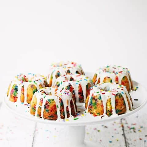 Mini Funfetti Bundt Cake with Vanilla Glaze -- Mini funfetti bundt cakes with vanilla glaze are a fun party dessert. Perfect topped with a scoop of ice cream, whipped cream, more sprinkles and a cherry! | halfscratched.com