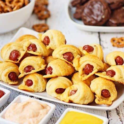 Cheesy Pigs in a Blanket + Sweet Sriracha Dipping Sauce -- After tasting these cheesy pigs in a blanket with sweet sriracha dipping sauce, you'll want to serve them at every game day party!   halfscratched.com