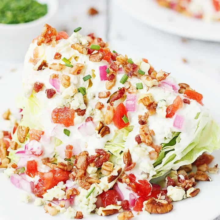 Loaded Wedge Salad -- This loaded wedge salad features iceberg lettuce topped with blue cheese dressing, red onion, tomatoes, bacon, blue cheese crumbles, and pecans. It's easier to make than you think! | halfscratched #recipe #salad