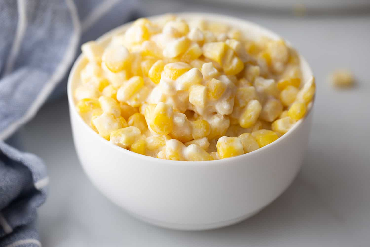 Easy Slow Cooker Creamed Corn - Ready for a side dish that's sure to please everyone? Try this easy, creamy, extra yummy slow cooker creamed corn! #creamedcorn #crockpot #slowcooker #sidedish #easyrecipe #slowcookercreamedcorn #corn #halfscratched