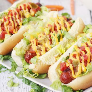 Spicy Bacon-Wrapped BLT Dogs -- Making bacon-wrapped hot dogs in the oven is easier than you think! Try this simple technique for bacon hot dogs as you throw together a batch of these spicy BLT dogs drizzled with melted cheese sauce. #halfscratched #hotdogs #blt #bacon #easyrecipe #maindish #bbq #barbecue #grilling