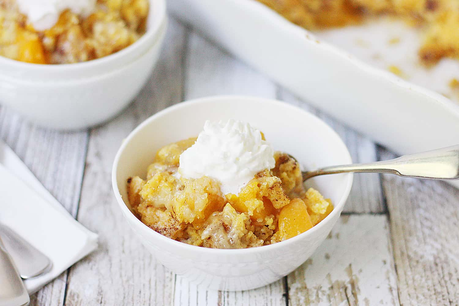 Easy Peach Cobbler Dump Cake -- Easy peach cobbler dump cake is sure to become a summer staple! This mouthwatering peach cobbler recipe requires only four ingredients and five minutes of prep! #cake #peachcobbler #dumpcake #dessert #easyrecipe #cakemix #cobbler #peach