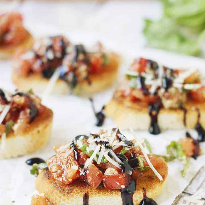 Easy Tomato Bruschetta Recipe - Top toasted baguette slices with this easy tomato bruschetta for an appetizer full of tomato, basil, balsamic flavor that is perfect for holiday parties! #bruschetta #tomato #halfscratched #appetizer #tomatobruschetta #cooking #baking #easyrecipe #holidayrecipe