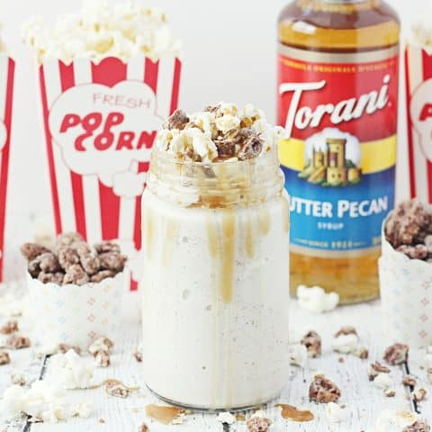 Take your stay-at-home movie nights up a notch with a kettle corn butter pecan shake! Vanilla ice cream, butter pecan syrup, and candied pecans are blended together and topped with kettle corn, more candied pecans, and a drizzle of caramel syrup. #FallforFlavor #Torani #halfscratched #butterpecan #kettlecorn #milkshake #dessert #dessertrecipe #shakerecipe #movietreat #treats #frozentreats #icecream #ad