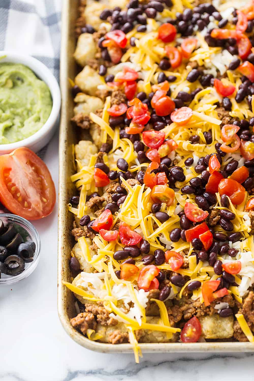 Tater Tot Nachos (Totchos) - What's better than crispy, crunch tater tots topped with oh-so-flavorful nacho fixings? Nothing! That's why tater tot nachos, aka totchos, are always a hit! #nachos #tatertots #tatertotcasserole #appetizer #baking #cooking #easyrecipe #halfscratched #tatertotnachos #mexicanfood
