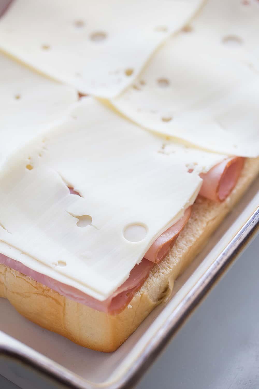 Hawaiian Ham & Cheese Sliders - Need a tasty way to use leftover ham or a recipe that'll feed a crowd? Look no further than Hawaiian ham and cheese sliders! #sliders #leftoverham #easyrecipe #hamandcheesesliders #maindish #baking #partyrecipe #holidayrecipe #halfscratched