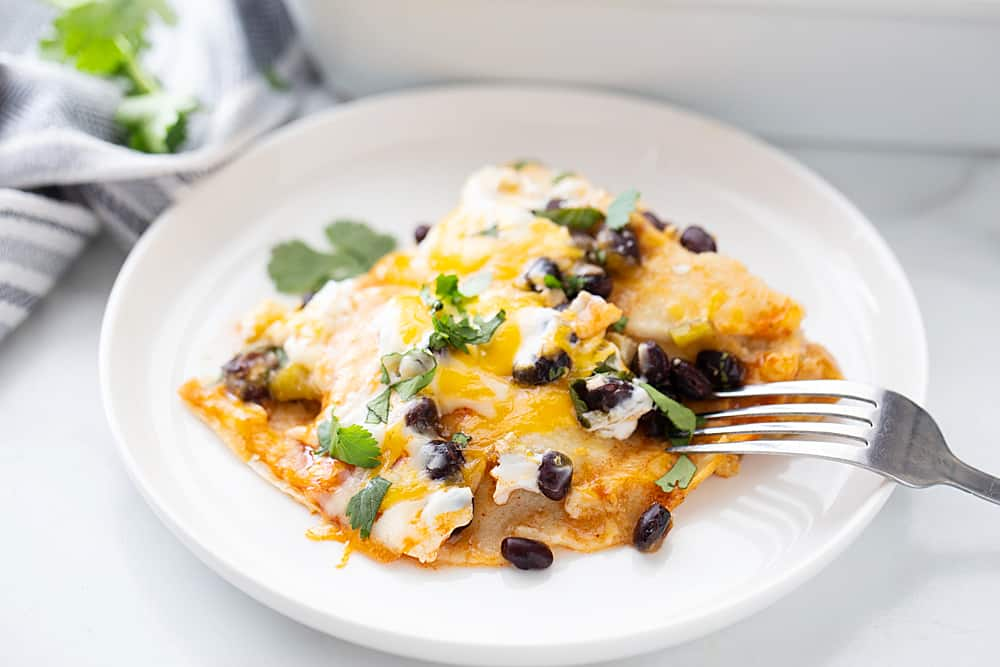 Layered Black Bean Enchiladas - When you don't have the time for classic chicken enchiladas, try these layered black bean enchilads. Quick, easy, and delicious! #enchiladas #mexicanrecipe #mexicanfood #blackbean #halfscratched #tacotuesday #easyrecipe #enchilada