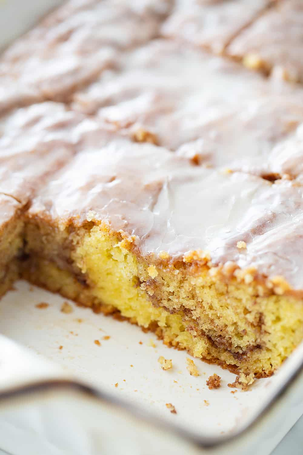 There's nothing like hot, cinnamon-swirled yellow cake topped with powdered sugar icing. Dessert or breakfast? Honey bun cake is both! #honeybun #cinnamonroll #cakemix #cakemixrecipe #honeybuncake #baking #dessert #brunch #halfscratched #yellowcake #easyrecipe