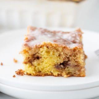 Honey Bun Cake - There's nothing like hot, cinnamon-swirled yellow cake topped with powdered sugar icing. Dessert or breakfast? Honey bun cake is both! #honeybun #cinnamonroll #cakemix #cakemixrecipe #honeybuncake #baking #dessert #brunch #halfscratched #yellowcake #easyrecipe
