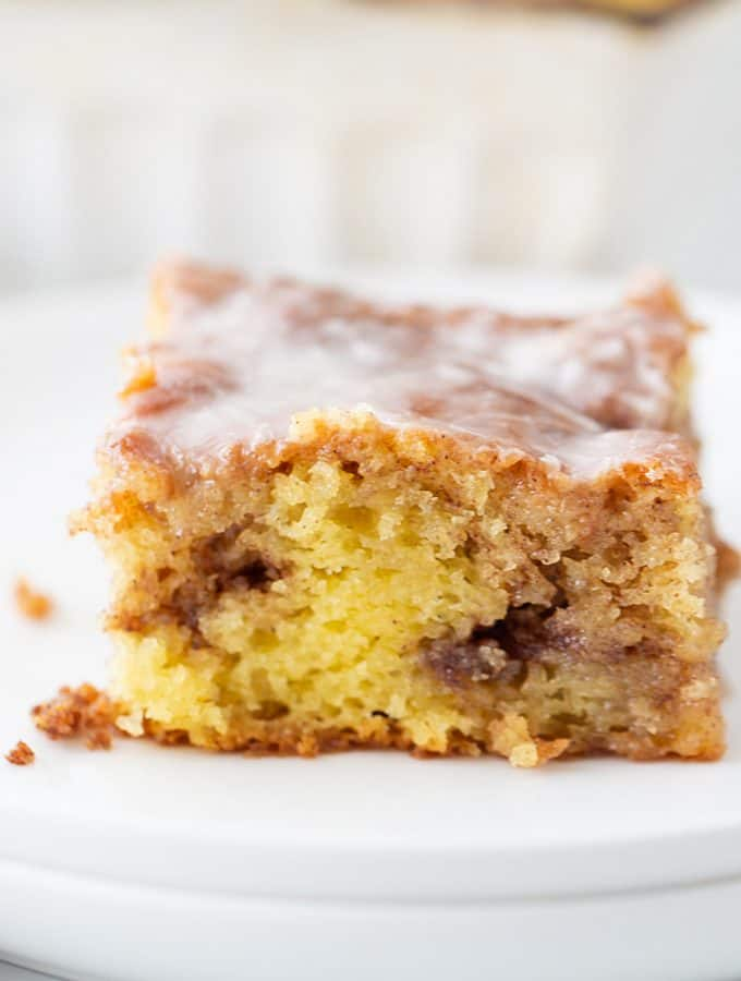 Honey Bun Cake - There's nothing like hot, cinnamon-swirled yellow cake topped with powdered sugar icing. Dessert or breakfast? Honey bun cake is both! #honeybun #cinnamonroll #cakemix #cakemixrecipe #honeybuncake #baking #dessert #brunch #halfscratched #yellowcake #easyrecipe