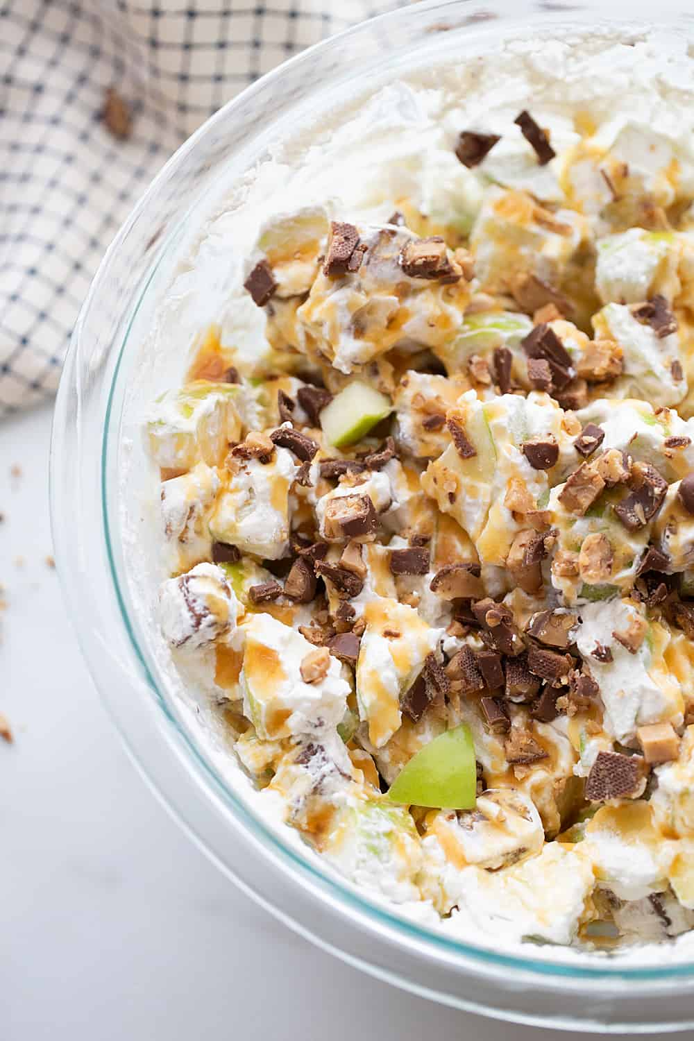 Easy Snickers Salad - This easy Snickers salad features Granny Smith apples, Snickers, and whipped topping with a drizzle of caramel and a sprinkle of toffee bits. #snickers #salad #dessert #halfscratched #easyrecipe #dessertsalad #sweets