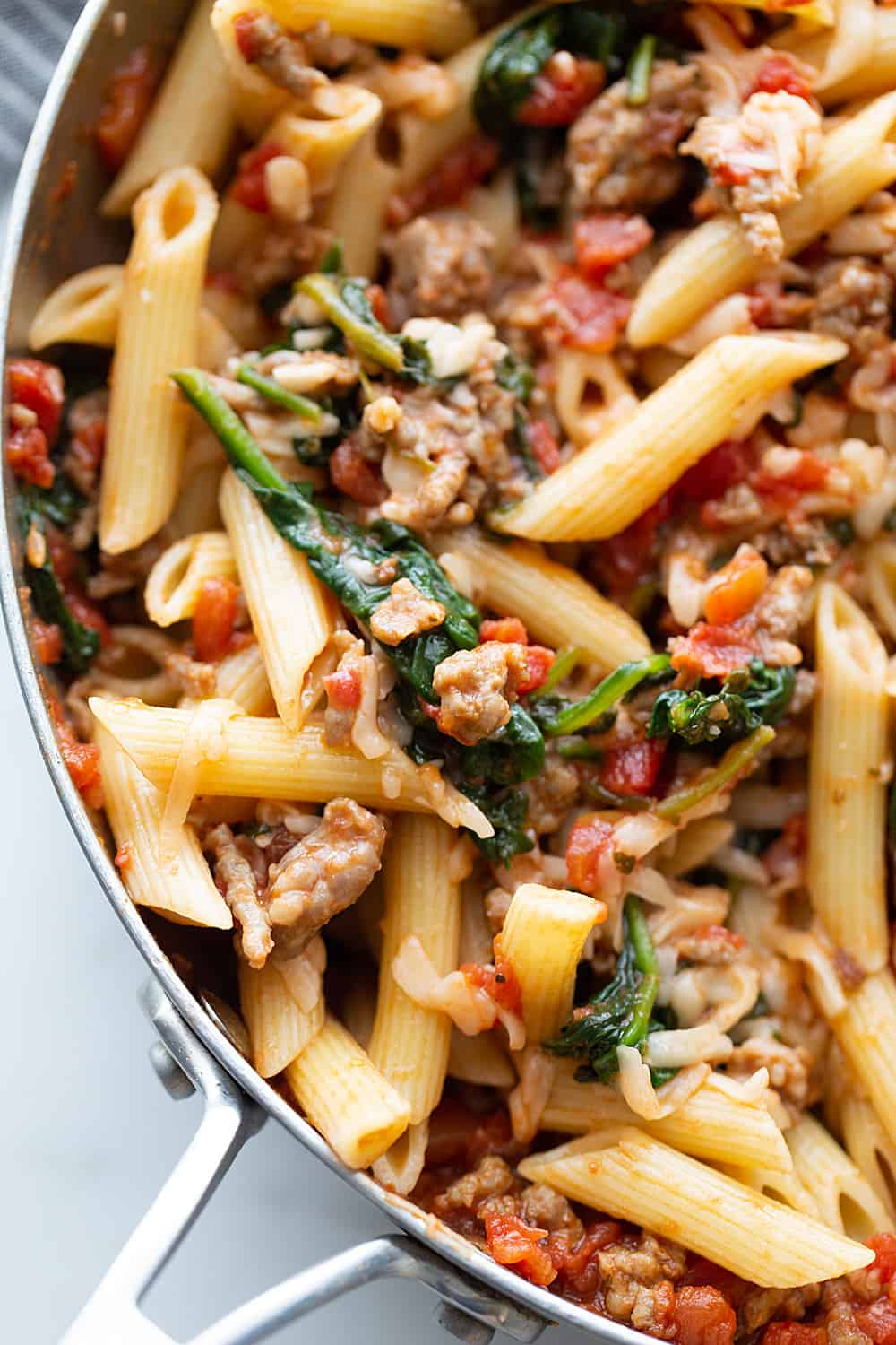 Tomato and Spinach Pasta Toss - With this easy tomato and spinach pasta toss recipe in your rotation, you can have a delicious, hearty meal ready in minutes! #pasta #italianfood #halfscratched #tomato #spinach #pastarecpie #maindish