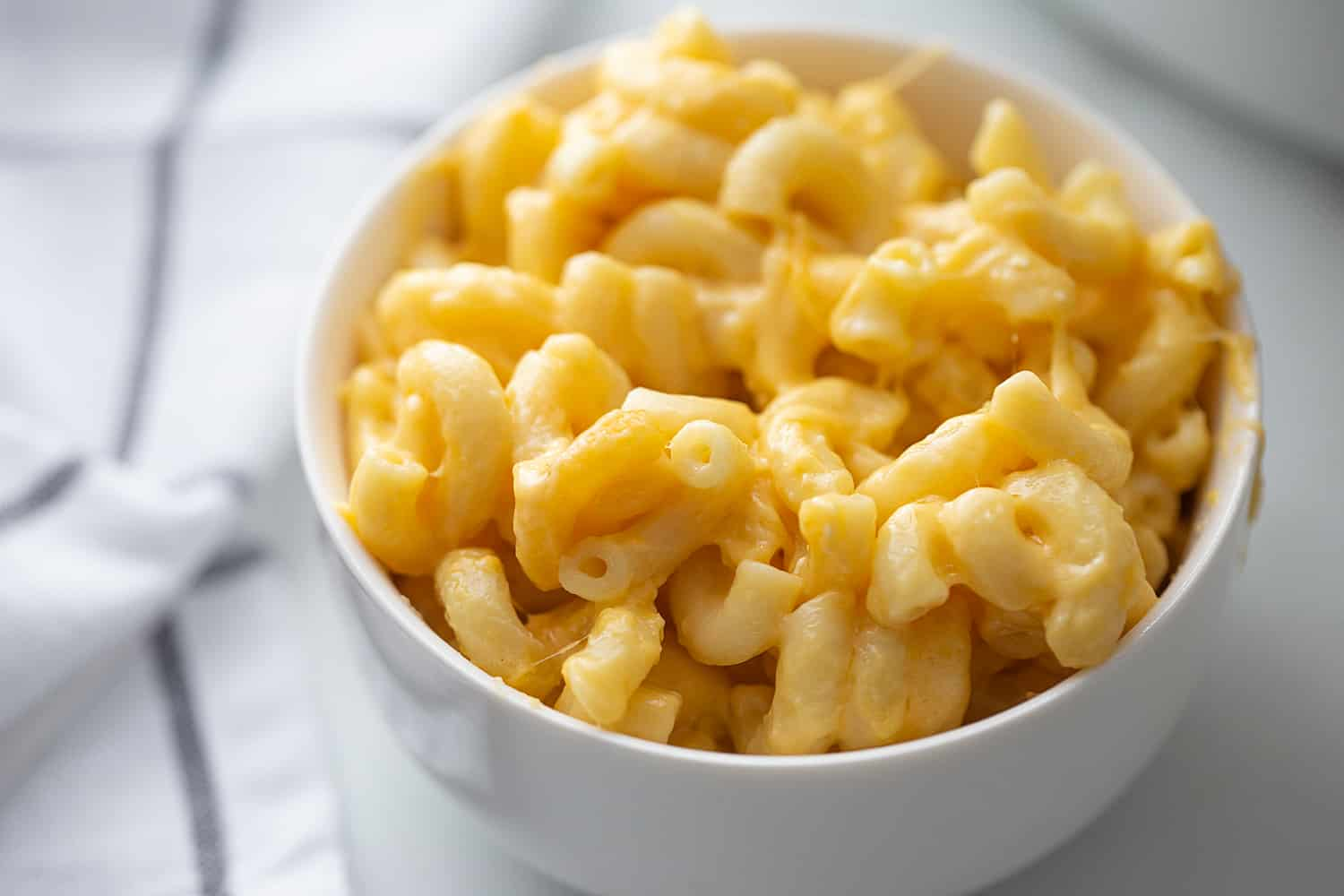 Easy Slow Cooker Mac and Cheese - Even the pickiest eaters will love easy slow cooker mac and cheese: a combo of sharp cheddar and Colby Jack plus a few surprise ingredients. #macandcheese #easyrecipe #halfscratched #slowcooker #pasta